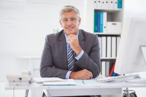 a business benefits consultant sitting at his desk waiting for a client to come in to discuss self funding insurance