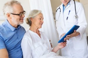 elderly couple discussing with a doctor and a Fairfax, VA benefits consultant about potentially switching to a direct primary care plan
