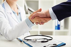 businessman shaking hands with a good doctor that he found through his group health insurance plan provided by his company