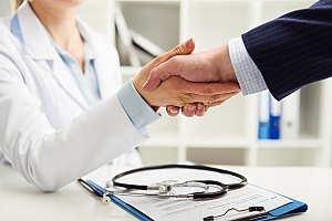 a medical doctor shaking hands with a benefits consultant who will discuss medical loss ration rebates with an insurance agent