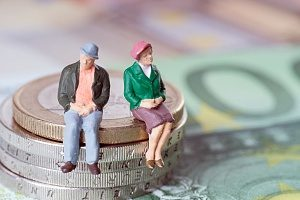 figurines of a couple sitting on a stack of coins to resemble health insurance for couples