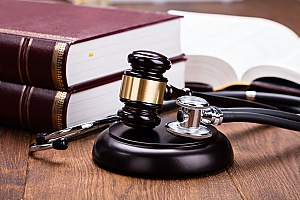 a gavel and stethoscope striking a block to sybolize how medical malpractice can be covered by malpractice insurance in terms of lawsuits