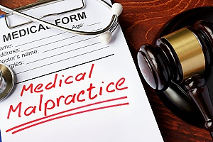 a medical malpractice booklet next to a gavel to show the importance of having malpractice insurance