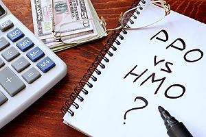 PPO vs HMO health insurance written on a piece of paper next to a calculator and a stack of money to represent how important health insurance is to any size business