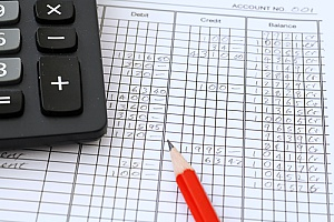 a pencil paper and calculator being used by a business consulting firm as they are calculating sellers discretionary earnings during a business valuation