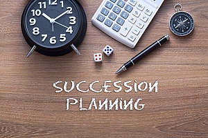 an alarm clock next to a pen and a calculator to represent how succession planning will help greatly benefit a business in the future