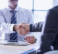 one of the business consultants at a business consulting firm shaking hands with a small business owner as they discuss the types of business insurance offered