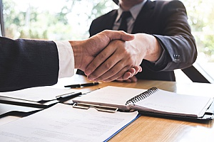 a business consulting firm shaking hands with a business owner during their business valuation meeting
