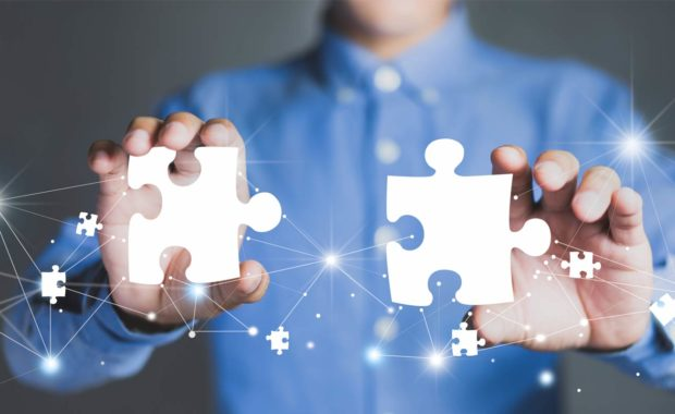Employee with puzzle pieces symbolizing a company merger