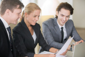 three business partners smiling while looking over the planned employee benefits package