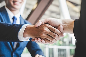 a current business owner shaking hands with a new business owner during business transfer