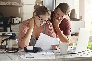 Stressed couple looking at bills