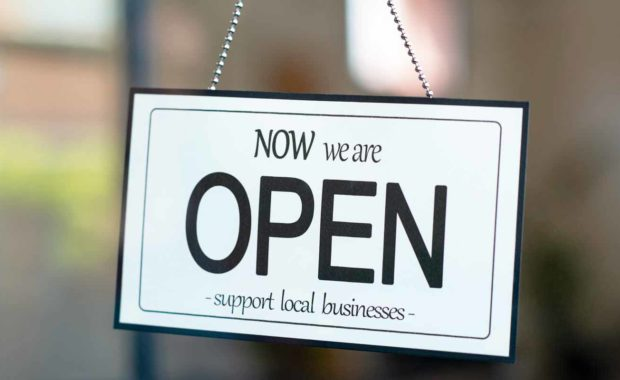 a-support-local-business-sign-with-the-words-now-we-are-open-after-addressing-employee-safety