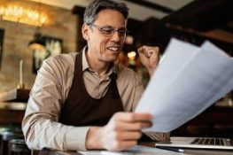 a business owner is elated analyzing his DBO insurance paperwork while working in a pub.
