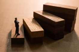 a figurine standing on the first step of wooden stair signifying business succession plan. Disability buy-out insurance protects business owners from certain disabilities.