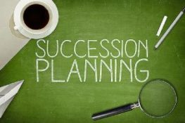 succession planning text written on green board. A cup of coffee, a magnifying glass, a paper plane and one each of a chalk and a pen is kept on each opposite corners.