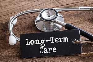 the words long term care with a stethoscope on a wooden table
