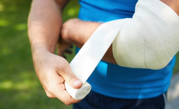 A man bandaging his arm. Short-term disability insurance can be invaluable when an employee experiences an accident