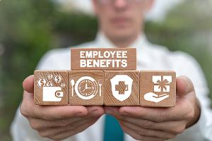 A person holding wooden cubes that has employee benefits icons. Benefits renewal can be a complex topic