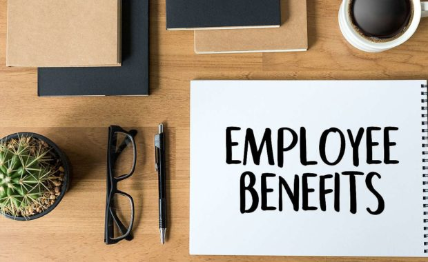 Employee benefits written on a notepad. Businesses will encounter regular benefits renewal periods