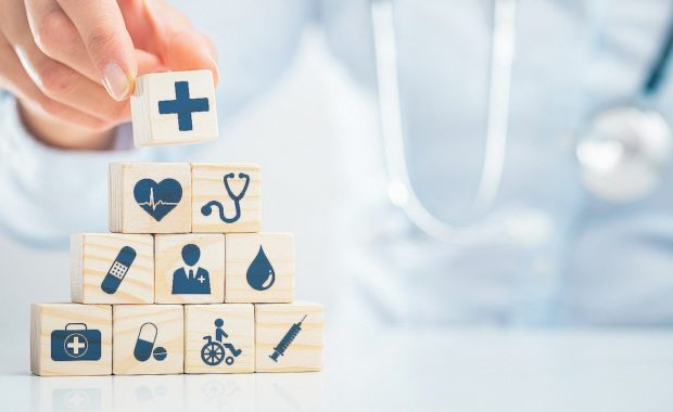 Hand arranging wood block with healthcare medical icon. EPO health insurance plan lower health care costs