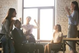Employees during a team meeting. Benefits renewal process involves all parties