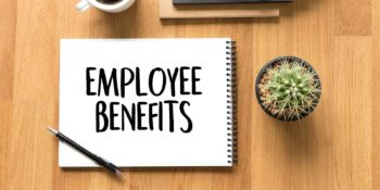 Word Employee benefits written on a notepad. Each year, employers are responsible for renewing employee benefits