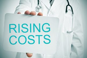 A doctor and rising cost written on a small placard depicting rising healthcare costs