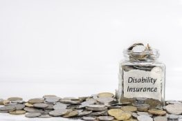 Coins with disability insurance labeled on a jar. Employee benefits package will foster a positive company culture