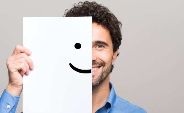 Man covering half his face with a smiling emoticon. Nonprofit employee benefits can attract new talent