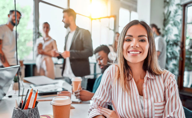women happy in office with her Government Contractor Employee Benefits