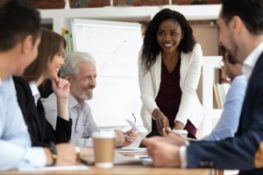 Diverse businesspeople gathered talking about their  Government Contractor Employee Benefits