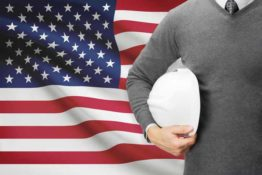 Man holding hard hat in front of flag