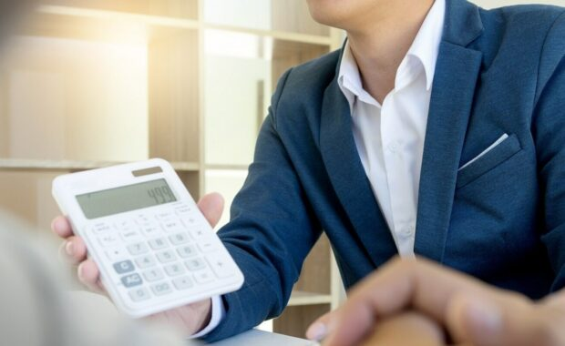 Insurance Premium Financing Work- Young Man Showing Calculator