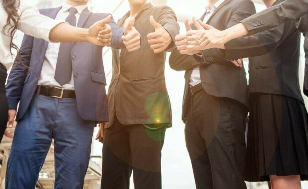 business partners giving thumb up bump after complete a deal