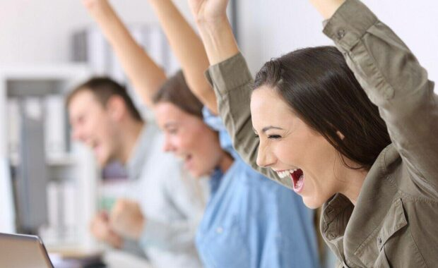 excited employees receiving good news on line in their laptops at office