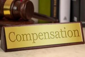 compensation written on wood board