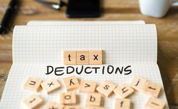 front focus on wooden blocks with letters making tax deductions text