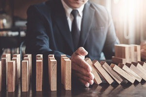 businessman protect wooden block fall to planning and strategy in risk to business