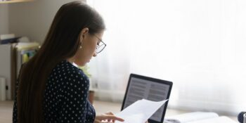 focused young woman in eyeglasses reading paper document
